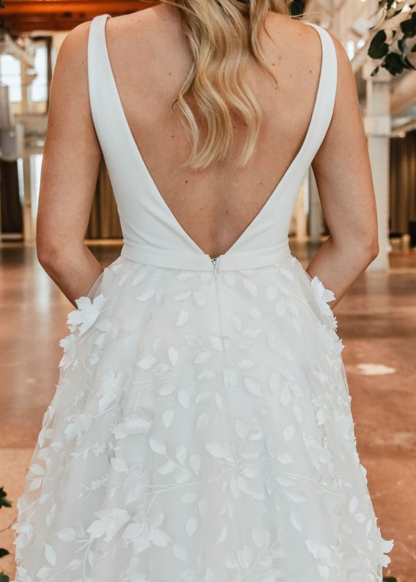 Blair - Colby John Bridal Couture at MaidenWhite in Las Vegas. Tank style straps with plunging neckline and v-back, full princess ball gown skirt with whimsical 3D floral details on the tulle skirt. Cathedral length train and hidden zipper.