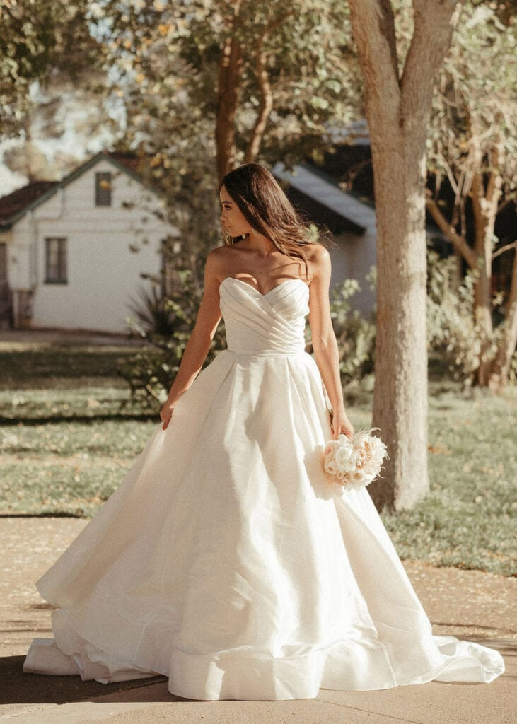 Mia - Colby John Bridal at MaidenWhite in Las Vegas. Strapless classic ball gown, princess. Clean, pearl shimmer organza. Sweetheart neckline with ruching at bodice.