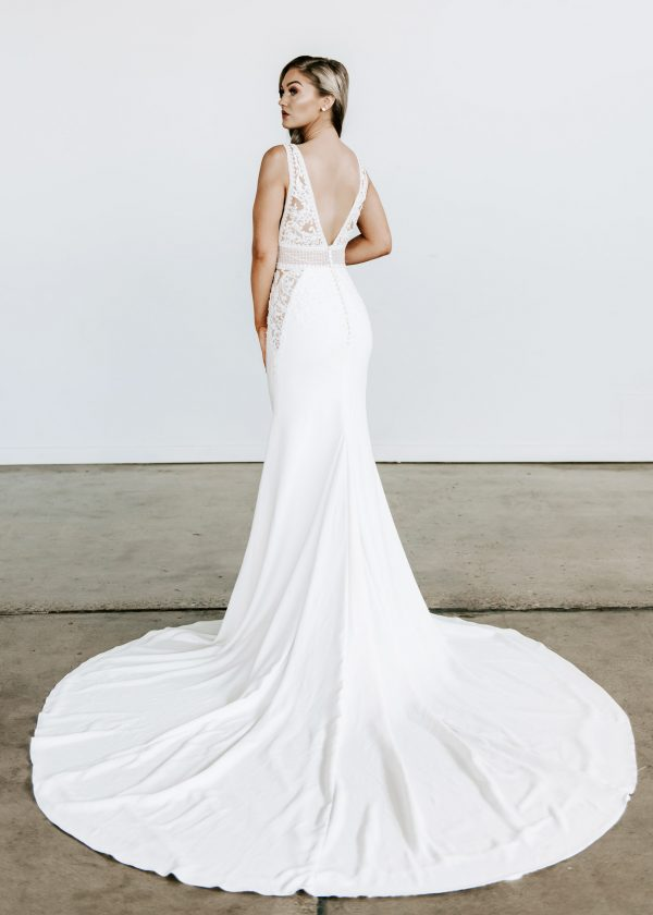 Aria - Colby John Bridal at MaidenWhite in Las Vegas. Tank style strap, sleeveless, plunging v neck and back, cathedral train. Crepe skirt, sheer illusion lace bodice with godet at waist.