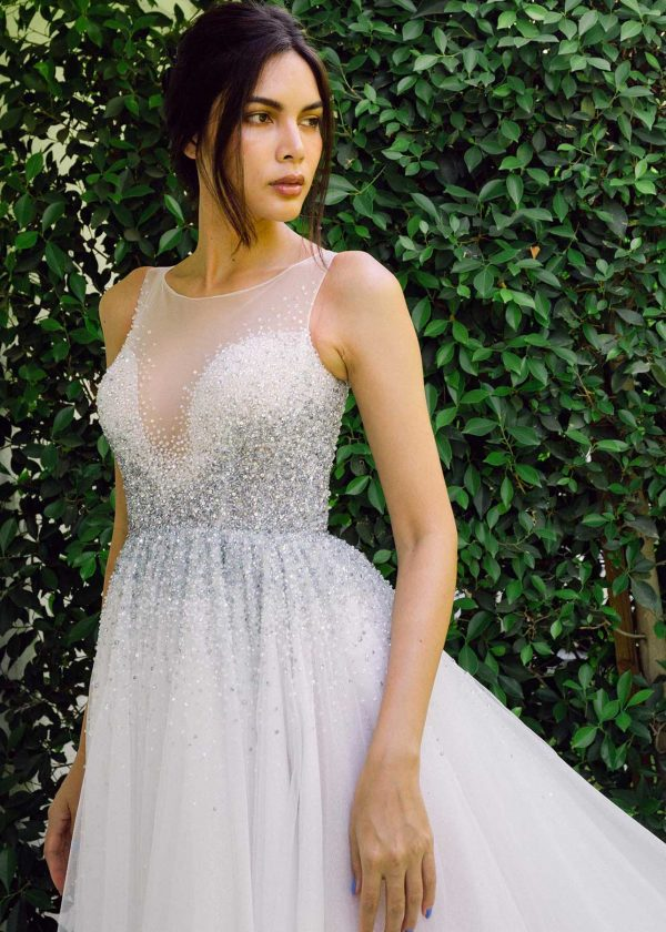 Aqua - Dany Tabet Couture at MaidenWhite in Las Vegas. Full ball gown princess silk tulle skirt. Shimmer sparkle glitter tulle. Tank style Straps, sheer high neckline and back with beaded ombre detailing down the bodice onto the skirt. Button closure.