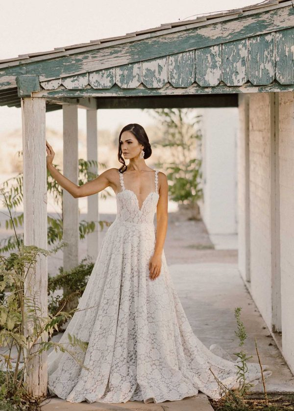 Alaska - Colby John Bridal at MaidenWhite boho bohemian spaghetti strap gown with floral details, knit floral lace, sparkle tulle, full a-line ball gown, n-neck, cathedral. length train. Buttons down back of the gown.