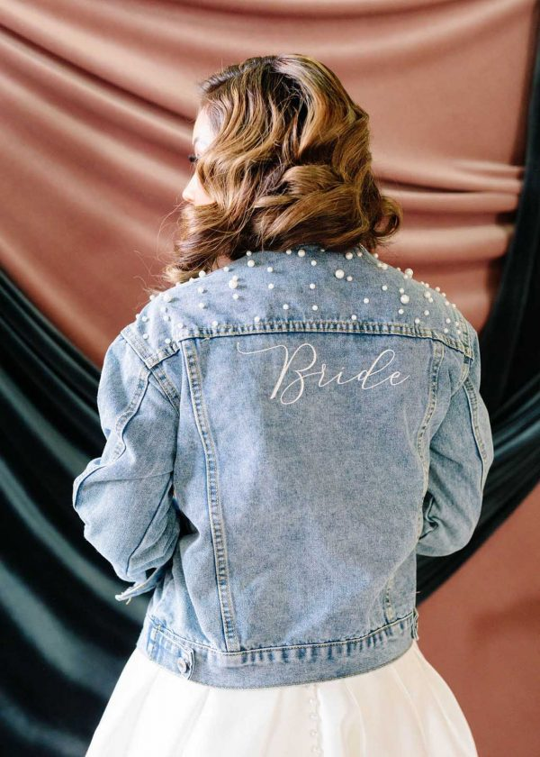 """Denim Pearl Jacket Back - MaidenWhite Exclusive Las Vegas. Crop denim with pearl details, embroidered """"Bride"""" ivory on back. Wedding gown bridal apparel accessories."""