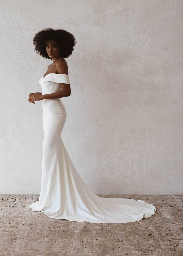 Lottie V2 - Made With Love Bridal at MaidenWhite in Las Vegas. Off the shoulder soft crepe, sweetheart neckline classic clean cathedral train. Boning in bodice figure hugging sheath trumpet luxury bridal gown.