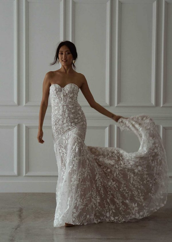 Penny - MWL Made With Love Bridal at MaidenWhite in Las Vegas. Strapless, sleeveless, sweetheart neckline luxury bridal gown. Nude tulle back, lace floral appliqués, fit n flare mermaid trumpet sheath. Cathedral train.