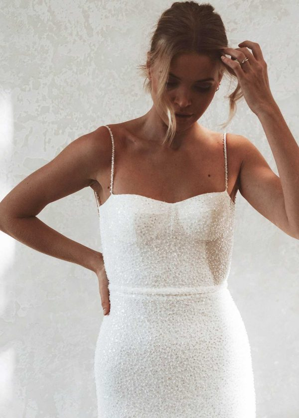Lola - MWL Made With Love Bridal at Maidenwhite in Las Vegas. Spaghetti strap fit n flare trumpet sheath, fully beaded ivory gown. Cup boning bodice for structure, low back with belt detail. Luxury wedding bridal gown.