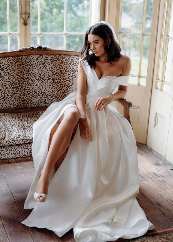 Francois - Hera Couture at MaidenWhite in Las Vegas. Off the shoulder strapless, sweetheart neckline, boning structured corset bodice, belted waist detail, silk drill satin. A-line skirt with thigh leg slit pearl details on back. Ivory couture luxury bridal gown.