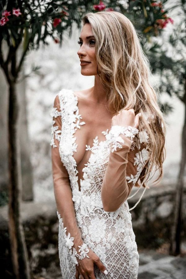 Rhiannon - Galia Lahav Couture at MaidenWhite in Las Vegas. Long sleeve lace illusion open back beaded detailing. Silk tulle with netted lace overlay. Deep V neckline, floral lace. Ivory white dress. Luxury Bridal gowns.