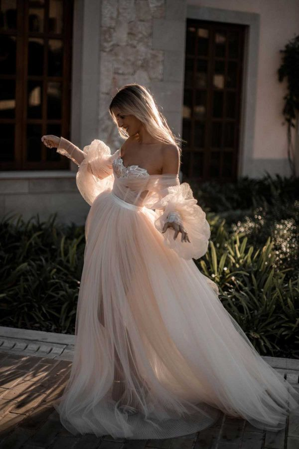 Bellina - Galia Lahav couture at MaidenWhite in Las Vegas. Off the shoulder, long sleeve blush gown. Sweetheart neckline with hand beaded details. A-line, princess ball gown, long balloon sleeves. Corsetry, boning in bodice.